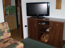Obývací pokoj s 2x pohovkou, stolem, židlí, skříňkou a televizí