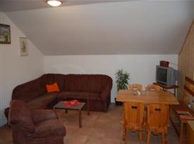 Společenská místnost  se sedací soupravou, jídelním koutem a televizí