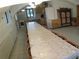 Společenská místnost s kuchyní, stoly, sedací soupravou a televizí
