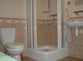 Koupelna na patře s toaletou, sprchovým koutem, umývadlem a zrcadlem