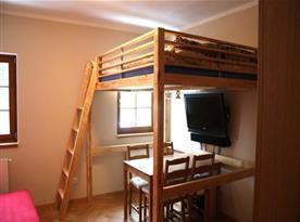 Obytná místnost s lůžky, posezením a televizí