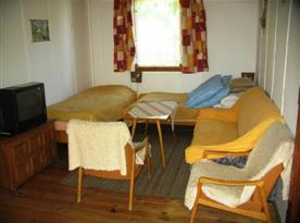 Obývací místnost s lůžky, posezením a televizí