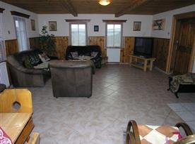 Společenská místnost s koženou sedačkou a televizí