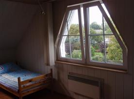 Ložnice s lůžky a výhledem na zahradu