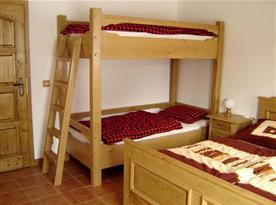 Ložnice v přízemí s manželskou postelí a palandou