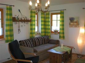 Společenská místnost s pohovkou, křeslem a stolkem