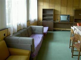 Pohled na společenskou místnost se sedací soupravou a televizorem