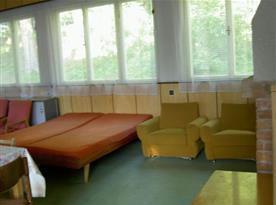 Pohled na společenskou místnost s křesly a lůžky