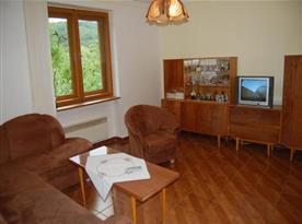 Obývací pokoj s posezením, televizí a pěkným výhledem na okolí