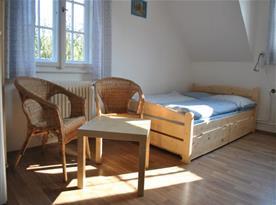 Pohled na pokoj s manželským lůžkem a posezením