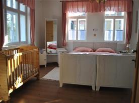 Pohled na ložnici s manželským lůžkem, dětskou postýlkou a zrcadlem