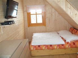 Podkrovní pokoj s televizí, komodou a lůžky
