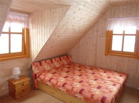 Pokoj v podkroví s lůžky, nočními stolky a televizí