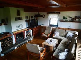 Pohled na společenskou místnost s krbem, posezením a televizí