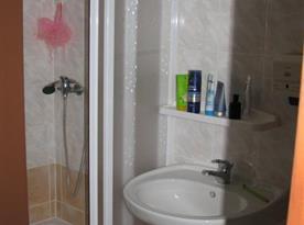 Koupelna se sprchovým koutem, umyvadlem a pračkou