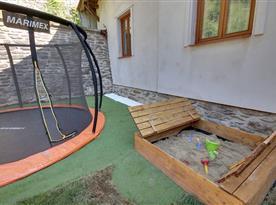 Zahrada s trampolínou a pískovištěm