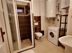 Koupelna s toaletou, sprchou a pračkou