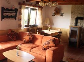 Obývací pokoj s krbem, televizí, posezením a jídelním koutem