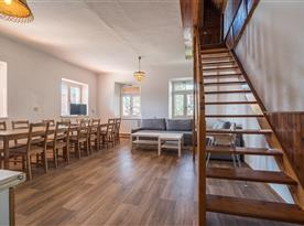 Společenská místnost s kuchyní a schody do podkrovní ložnice