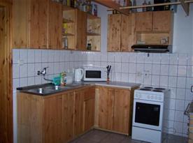Kuchyně se sporákem, varnou konvicí, lednicí a mikrovlnkou