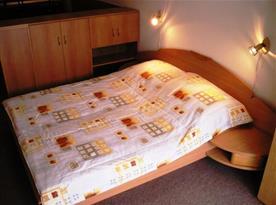 Ložnice s manželskou postelí, nočními stolky, skříní, televizí a CD přehrávačem