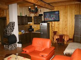Společenská místnost s kuchyní, sedací soupravou, televizí a krbovou pecí